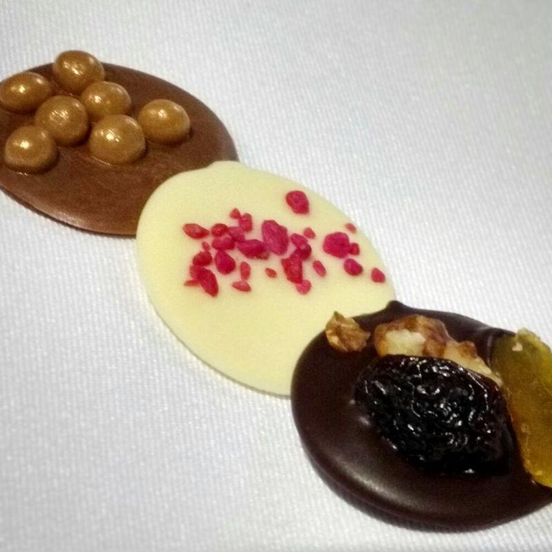 Mediant ( Medalha de chocolate ao leite com crisp flor de sal de caramelo, chocolate branco com cristais de rosas, chocolate amargo com frutas secas)
