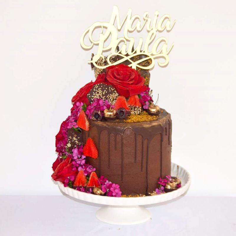 Pastel de chocolate semiamargo y frutos rojos decorado con bouquet de rosas y flores frescas