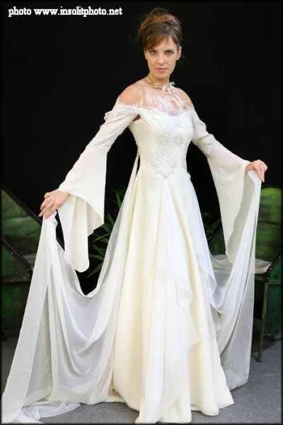 Modèle solstiss C'est une robe de mariage médiévale en mousseline de soie ivoire. Son bustier est agrémenté de dentelle de Calais ivoire et argent et de plumes.  Une véritable tenue de fée ou elfe, la légèreté d'un souffle. Création LEA MADELEINE Couture.  Le photographe est Marc Lucascio