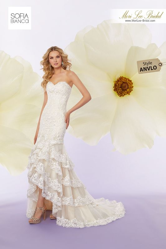Style ANVLO Selina  Crystal beaded, embroidered lace appliqués on a hi-low tulle gown trimmed with lace edged flounces