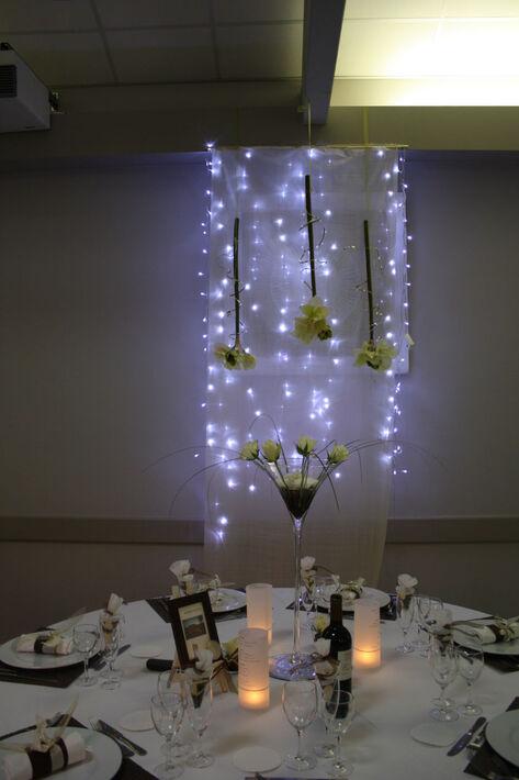 Table des mariée ponctuée par des guirlandes lumineuses clignotantes.