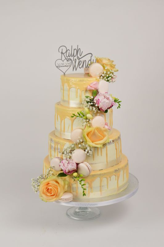 Semi naked weddingcake met een chocolade dripp en waterval van echte bloemen en macarons.