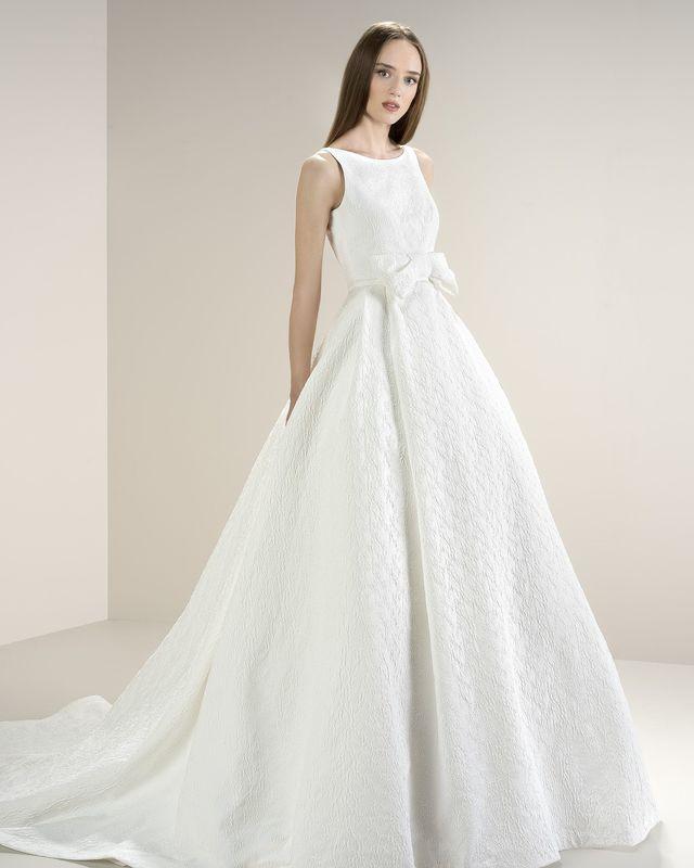Платье А-силуэта, выполнено из жаккарда с флористическими мотивами. Пояс декорирован объемным бантом. Спина подчеркнута глубоким вырезом.