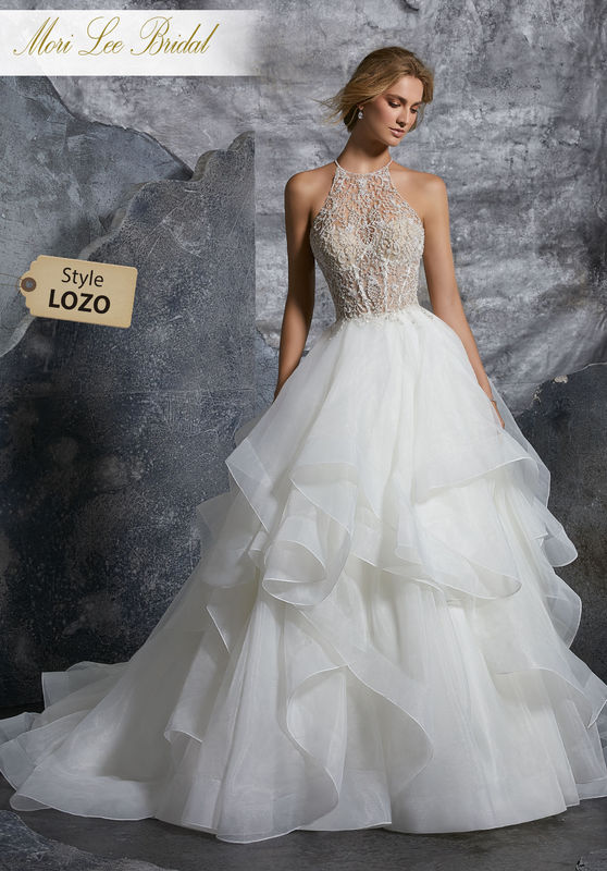 Style LOZO  Kali Wedding Dress  Dreamy Bridal Ballgown Featuring a Sheet Intricately Beaded and Embroidered High Halter Bodice with Flounced Organza Skirt. An Open Keyhole Back Trimmed in Covered Buttons Completes the Look. Matching Satin Bodice Lining Included Available in Three Lengths: 55″, 58″, 61″. Colors Available: White, Ivory, Ivory/Nude