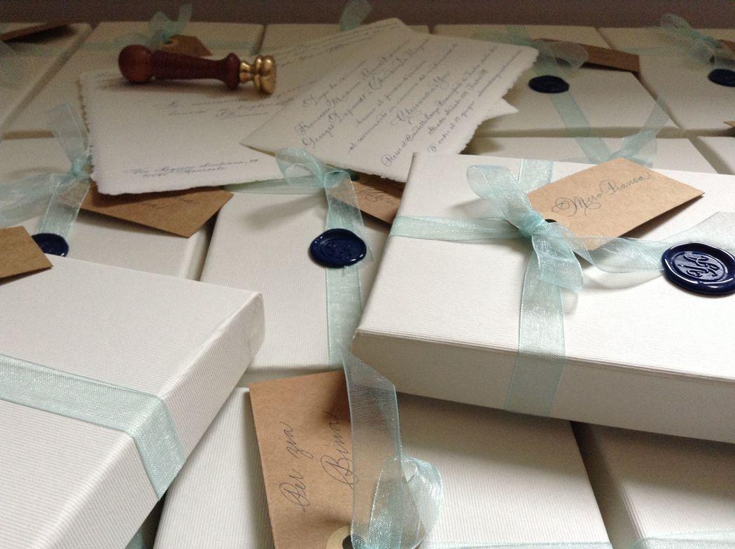 Il Calligrafo - Wedding boxes, su misura, contenenti inviti, colore avorio, con sigillo blu, nastro organza azzurro polvere e tags con intestazione ospiti in carta kraft.