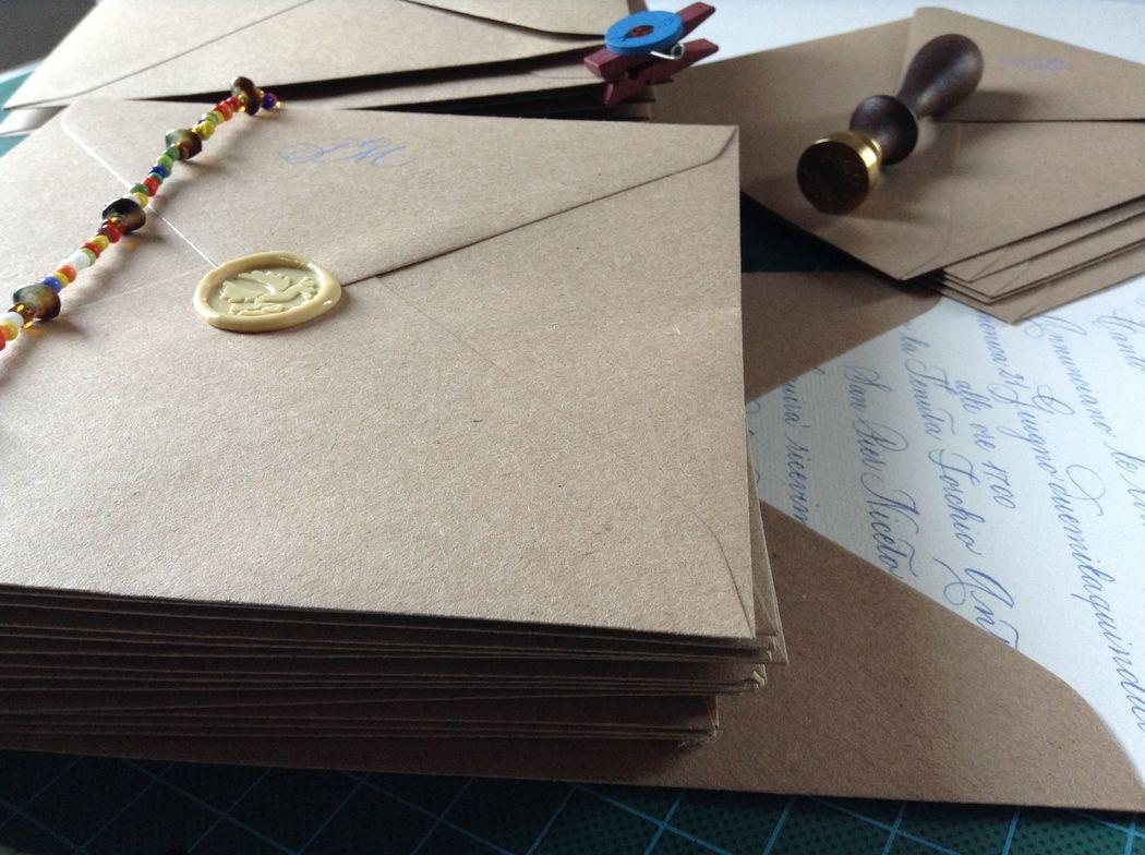 Il Calligrafo - Inviti carta a mano Amalfi avorio formato quadrato con busta in carta Kraft, manoscritti in azzurro con sigillo crema.