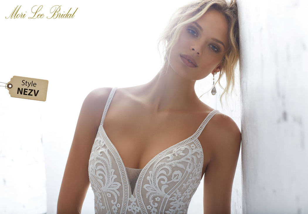 Style NEZV Kimora Wedding Dress  Striking Deco Medallion Embroidery Accents and Trims This Sultry Fitted Net Gown. A Scalloped Hemline and Sheer Train Complete the Look. Available inThree lengths: 55″, 58″, 61″. Colors Available: Diamond White, Ivory/Nude