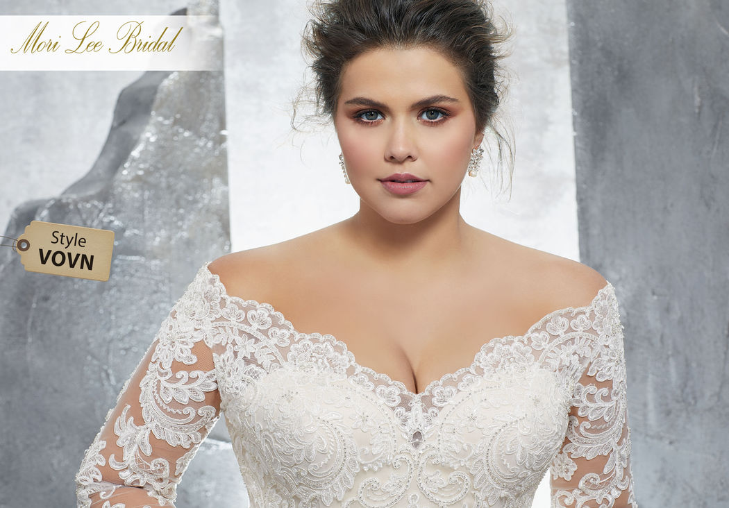Style VOVN Kameron Wedding Dress  Classic Long Sleeve Wedding Gown Featuring Crystallized Alençon Lace Appliqués and Medallions on Net. An Off-the-Shoulder Neckline and Scalloped Hemline Complete the Look. Available in Three Lengths: 55″, 58″, 61″. Colors Available: White, Ivory, Ivory/Coco